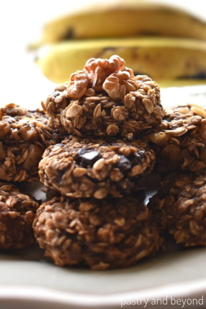 Stacked 3 ingredient banana oatmeal cookies on a plate with bananas in the background.