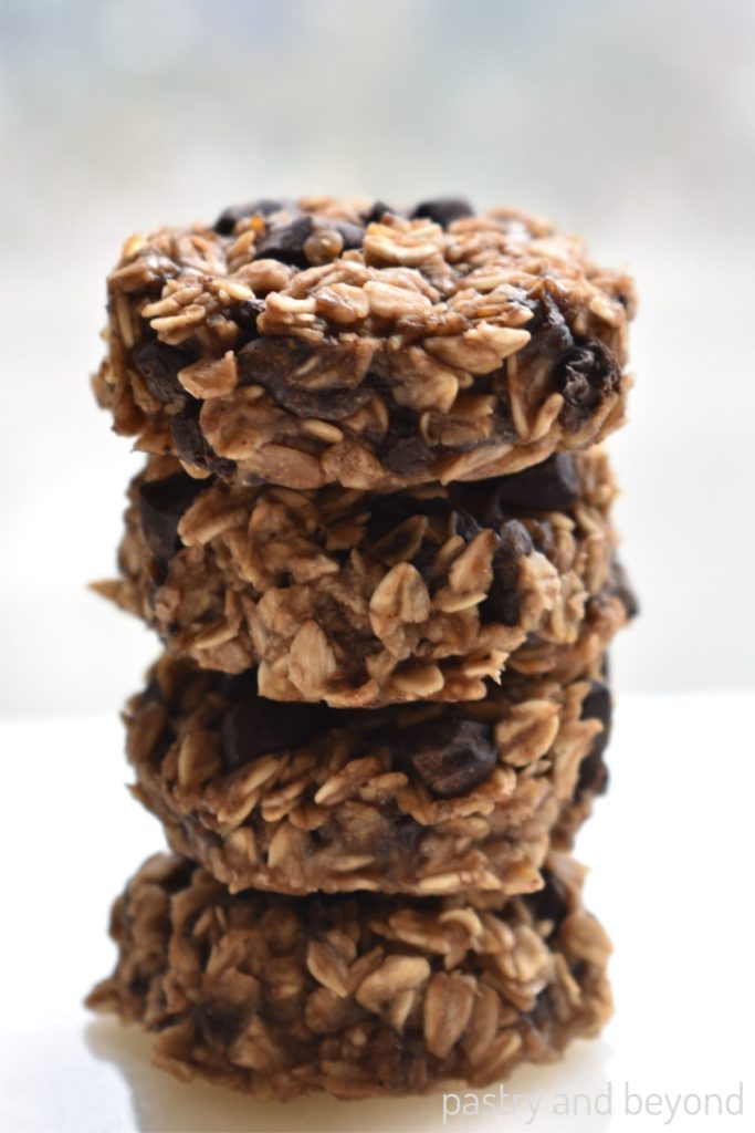 Stacked banana oatmeal cookies with chocolate chunks on a white surface.