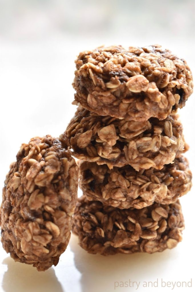 Stacked banana cinnamon oatmeal cookies on a white surface.
